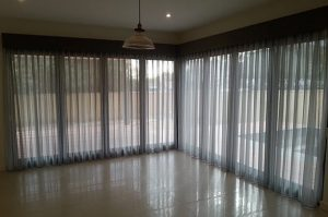 Pinch pleated sheer curtains with straight pelmet.