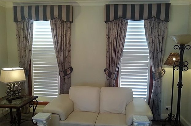 With pinch pleated curtains and tiebacks, in coordinating fabrics.