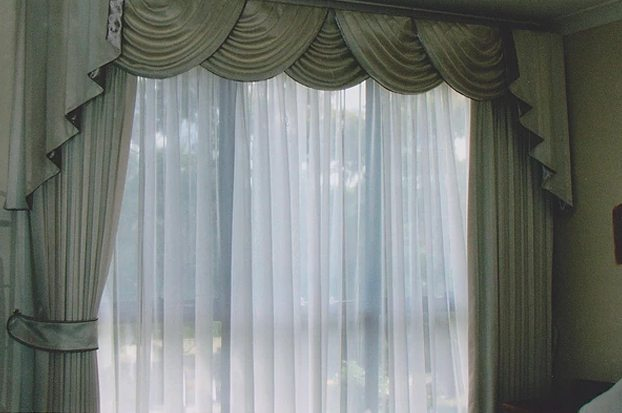 Over rod pocket sheers and pinch pleated curtains.