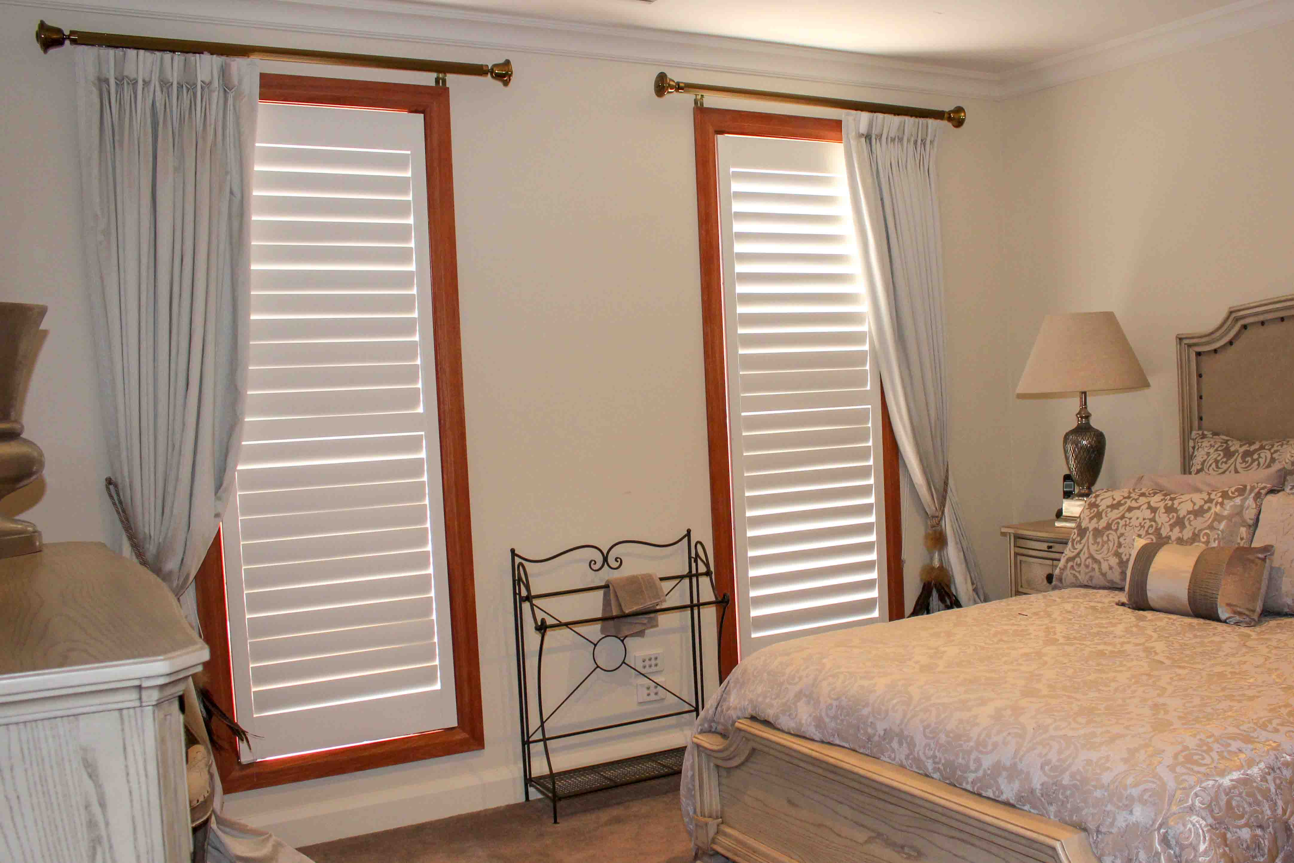 Goblet pleated lined curtains draped on floor. On decorative antique brass poles