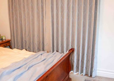 Pinch pleated lined curtains on decorative antique brass pole