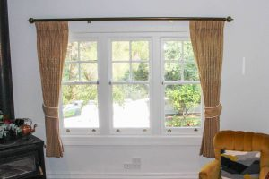 Pinch pleated lined curtains on decortaive antique brass poles, with tiebacks