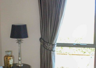 Pinch pleated lined curtains with padded pelmets and coordinating tiebacks