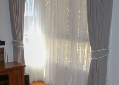 Pinch pleated lined curtains with padded pelmets, over sheer curtains for privacy.