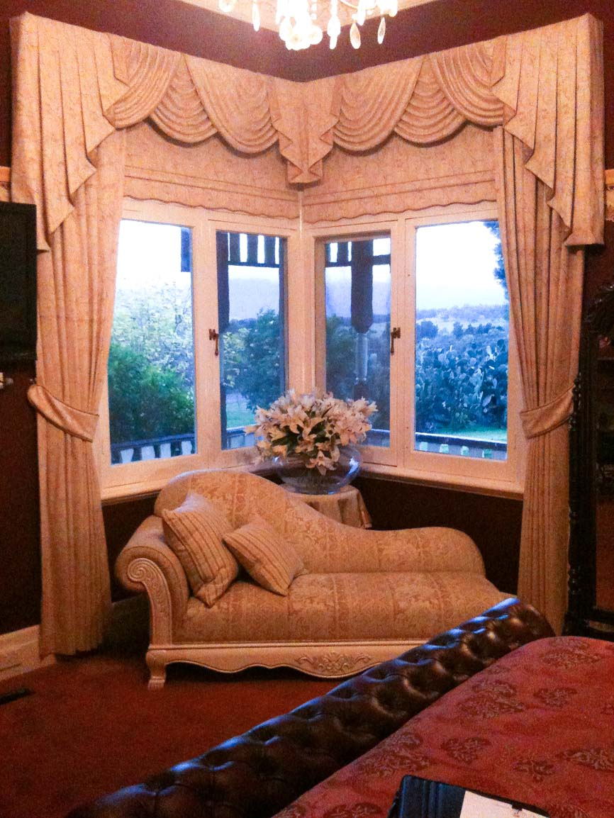 Traditional swags and tails over bonded roller blinds, side curtains and tiebacks