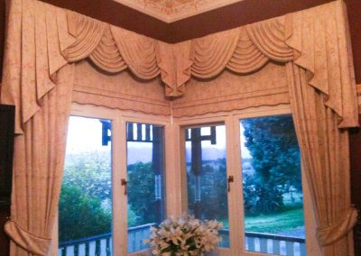 Traditional swags and tails over bonded roller blinds, side curtains and tiebacks_